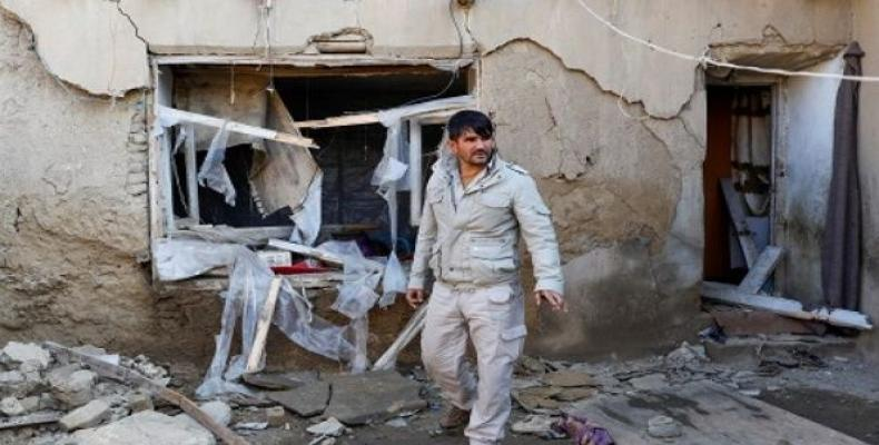 A man inspects a damaged house at the site of an attack in a U.S. military air base in Bagram. (Photo: Reuters)