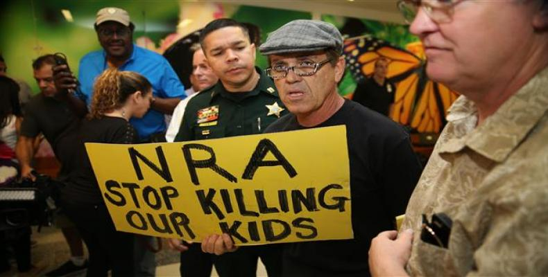 People protest against the National Rifle Association at the Broward County Court House during the first appearance in court via video link for high school shoo