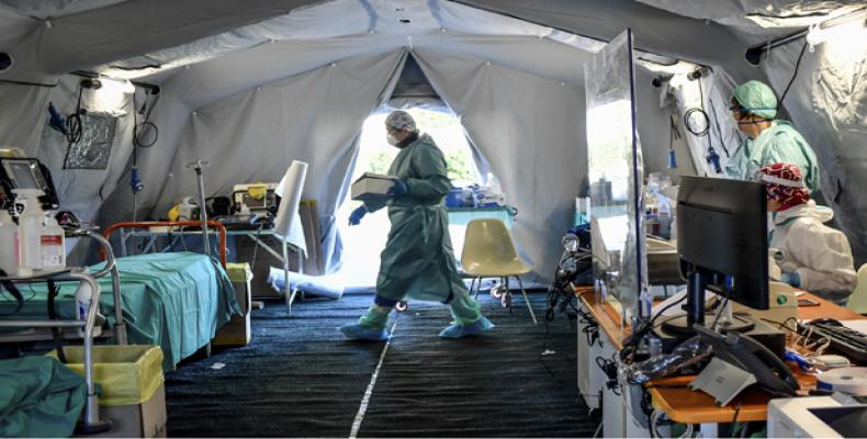 Medical personnel work inside one of the emergency structures that were set up to ease procedures outside the hospital of Brescia, Northern Italy, Tuesday, 10 M