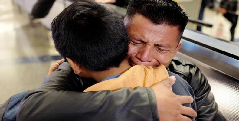 David Xol-Cholom from Guatemala hugs his son Byron at Los Angeles International Airport.  They were separated for nearly two years.  (Photo: Ringo HW Chiu/AP P