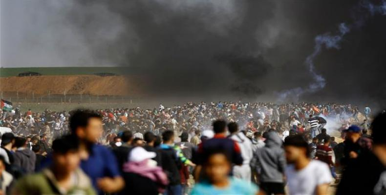 Palestinians run for cover from tears gas fired by Israeli forces during clashes following a protest on the Israel-Gaza border east of the Jabalia refugee camp