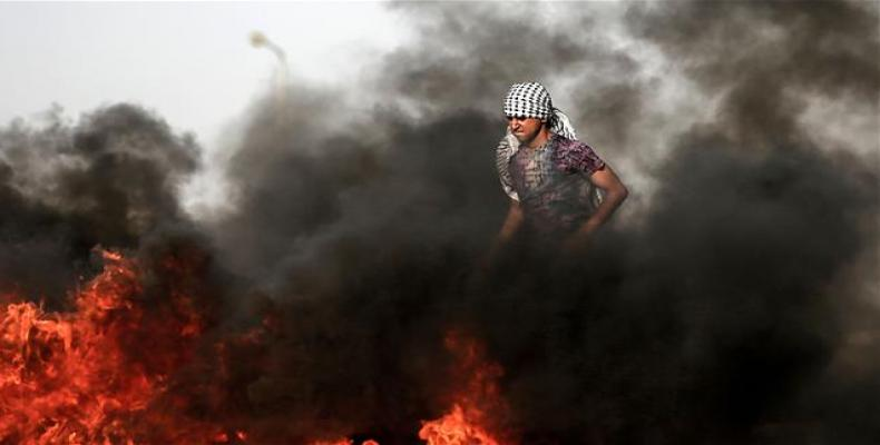 A Palestinian demonstrator walks in the smoke billowing from burning tires during clashes with Israeli forces along the border with the Gaza strip east of Gaza