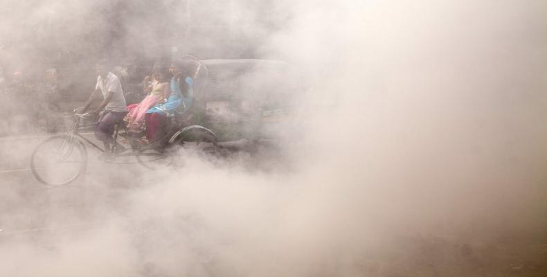 A Bangladeshi rickshaw puller rides past smoke created by burning waste materials on a street in Dhaka. Photograph: Anadolu Agency/Getty Images