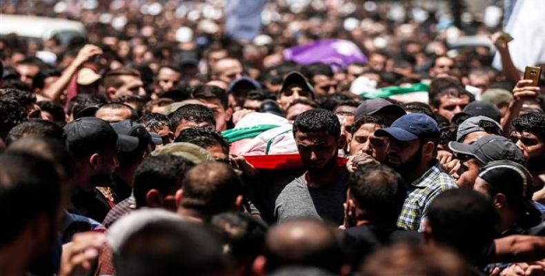 Palestinian mourners carry the body of a Hamas member killed by Israeli fire, during his funeral in Jabalia, in the northern Gaza Strip, on August 7, 2018.  Pho