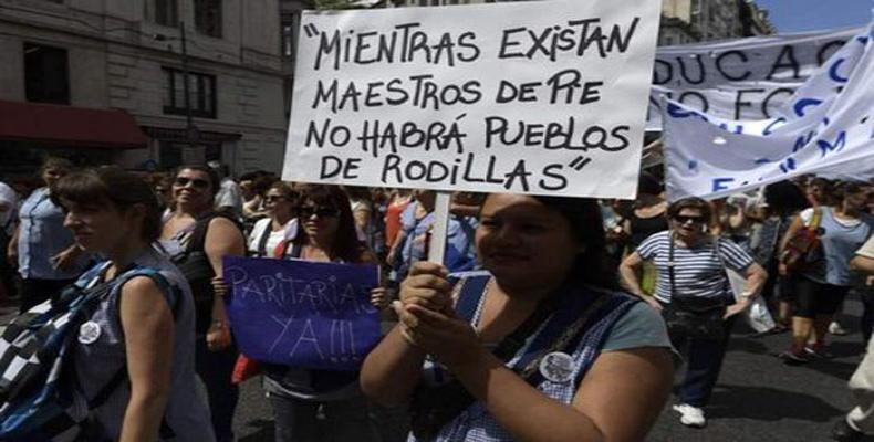 """""""Tant qu'il y aura des enseignants debout, il n'y aura pas de peuples à genoux"""" signale la pancarte."""
