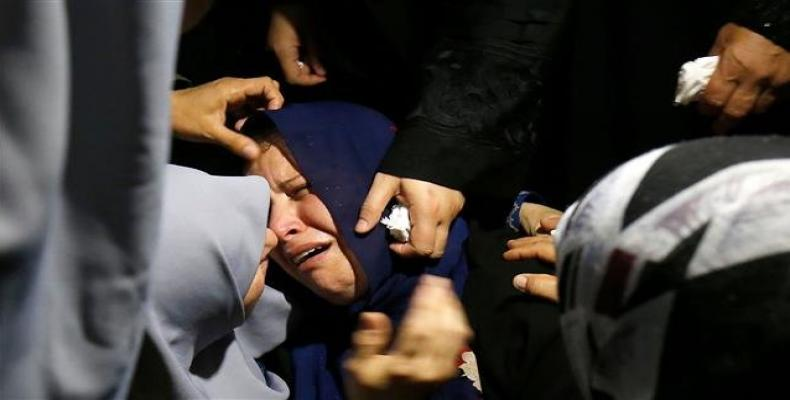 A Palestinian relative mourns over the death of Muadh al-Suri, aged 15, who was killed during clashes with Israeli forces the day before, during his funeral.  P