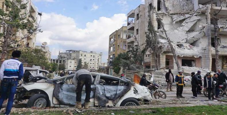 The wreckage of a car and a damaged building in the background are seen in Syria's militant-held city of Idlib on February 18, 2019, following a double bomb att