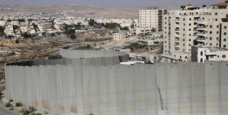 This picture shows the Israeli settlement of Pisgat Ze'ev (L) behind its controversial separation barrier on the outskirts of East Jerusalem.  Photo: AFP