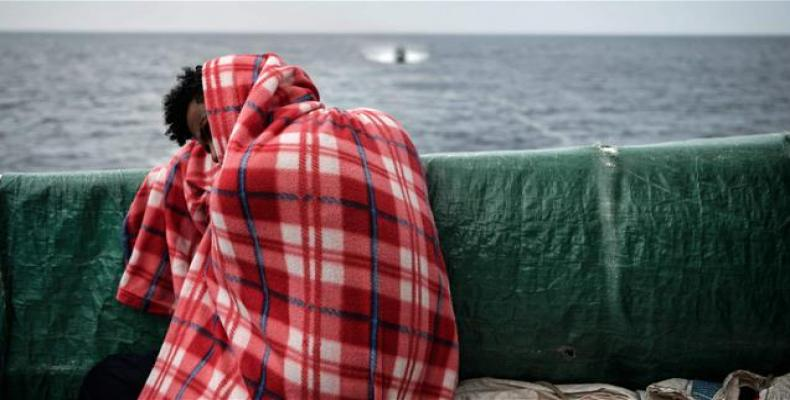 A refugee rests on the deck of the MV Aquarius as it sails into the Sicilian port of Messina.  Photo: AFP