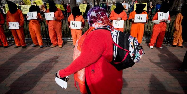 A woman walks past activists protesting the Guantanamo Bay detention camp during a rally in Lafayette Square outside the White House January 11, 2018 in Washing