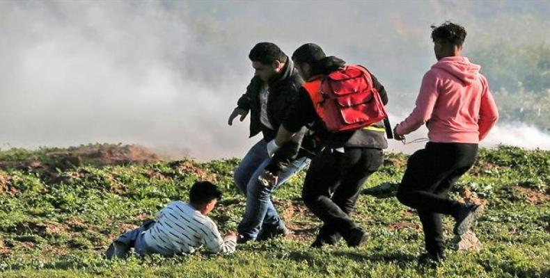 Palestinian protesters and a medic run to pick up a child during a demonstration east of Gaza City, February 22, 2019. Photo: AFP