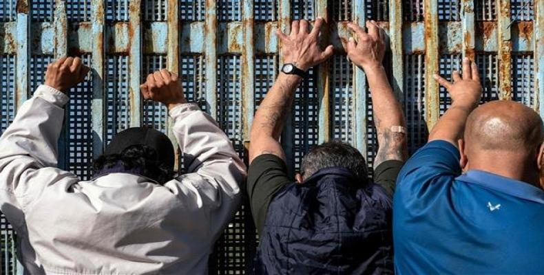 People lean against the US-Mexico border fence in Playas de Tijuana, Baja California state, Mexico on February 3, 2019.  Photo: AFP