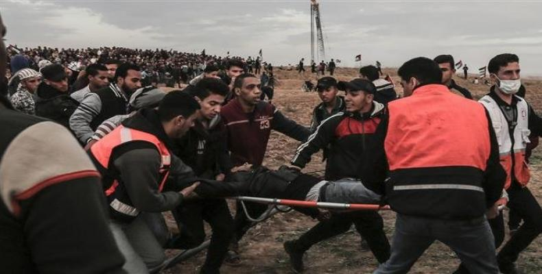 Palestinian men carry an injured man during a protest on November 16, 2018, on the eastern outskirts of Gaza City.  Photo: AFP