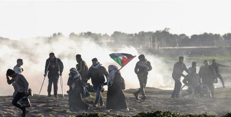 Palestinian protesters run away from teargas canisters during clashes with Israeli forces following a demonstration along the Gaza border east of Gaza City on J