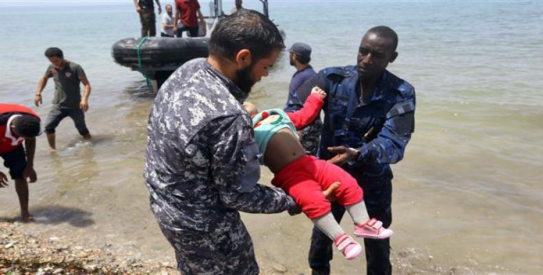 Members of Libyan security forces carry the body of a baby as refugees who survived the sinking of an inflatable dinghy off the coast of Libya are brought ashor