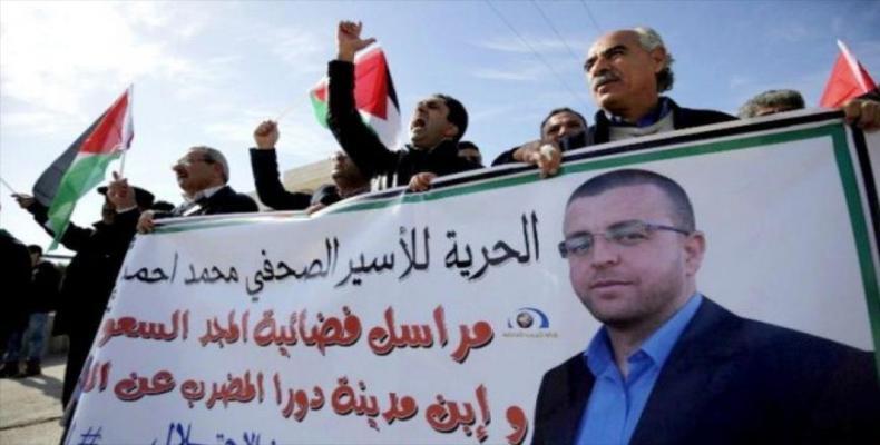 Manifestantes palestinos portan pancartas con la imagen del periodista preso en huelga de hambre, Mohamad Al Qig (hispantv.com)