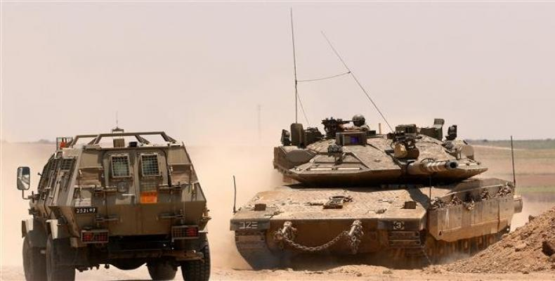 An Israeli army armored vehicle driving past a Merkava Mark IV tank taking position along the Gaza fence.  Photo: AFP