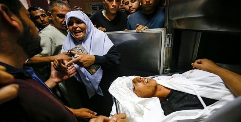 The aunt of slain 15-year-old Palestinian Ahmed Abu Habel killed during clashes with Israeli forces near a checkpoint in the northern Gaza Strip reacts by his b
