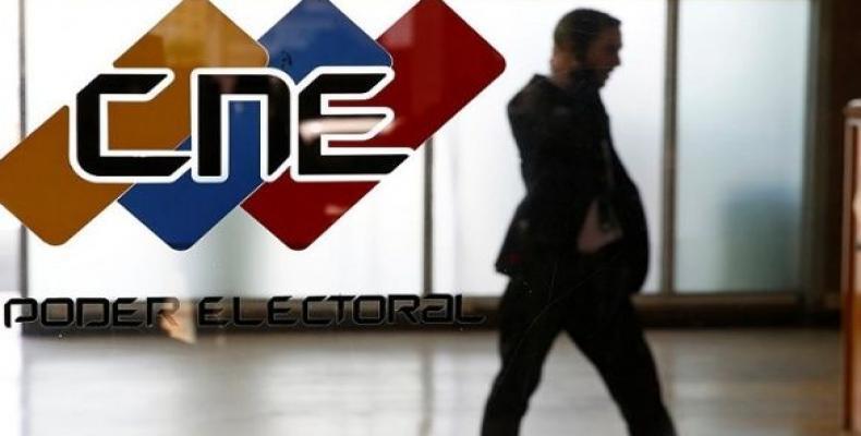 A man walks past a log of the Venezuelan National Electoral Council, CNE in Caracas.  Photo: Reuters