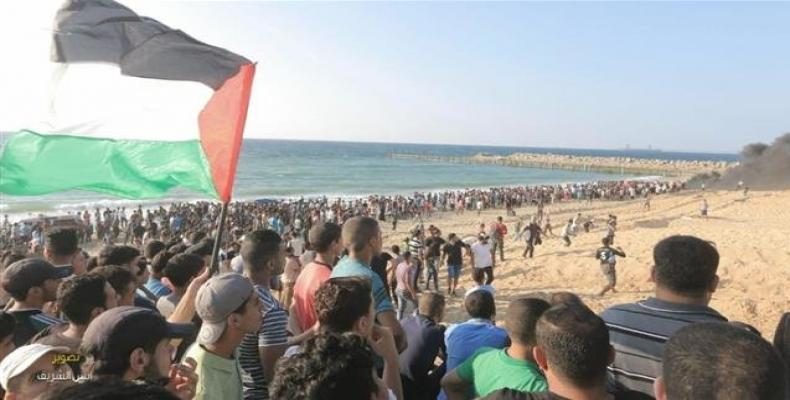 Palestinian protesters wave national flags as they participate in a demonstration on the beach near the maritime border with Israel, in the northern Gaza Strip,