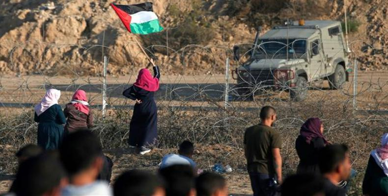 A Palestinian protester waves her flag during a demonstration along the fence with the occupied territories in central Gaza Strip. (Photo: AFP)