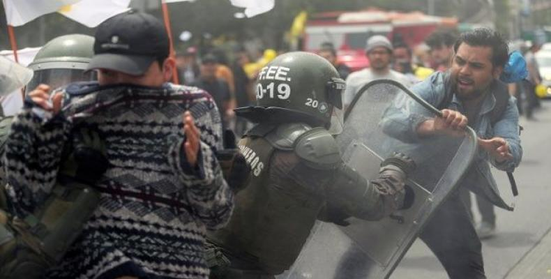 A demonstrator clashes with a riot policeman during a rally against Chilean pension fund administrators, in Santiago, Chile.  Photo: teleSUR