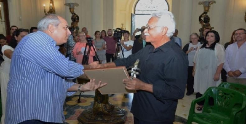 El ministro cubano de Cultura, Alpidio Alonso (I) entrega el lauro a Omar López (D). Foto tomada de Cubasí