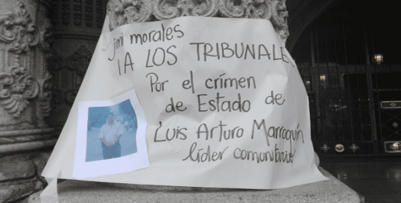 "A sign reads ""Jimmy Morales to court for the state crime against community leader Luis Arturo Marroquin,"" during a protest against the Guatemalan pres"