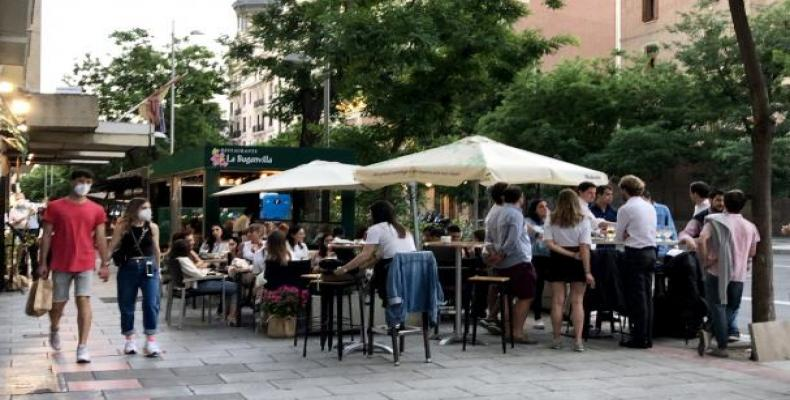 Varios jóvenes se reúnen en grupos en torno a las mesas de una terraza en Madrid.Jorge París