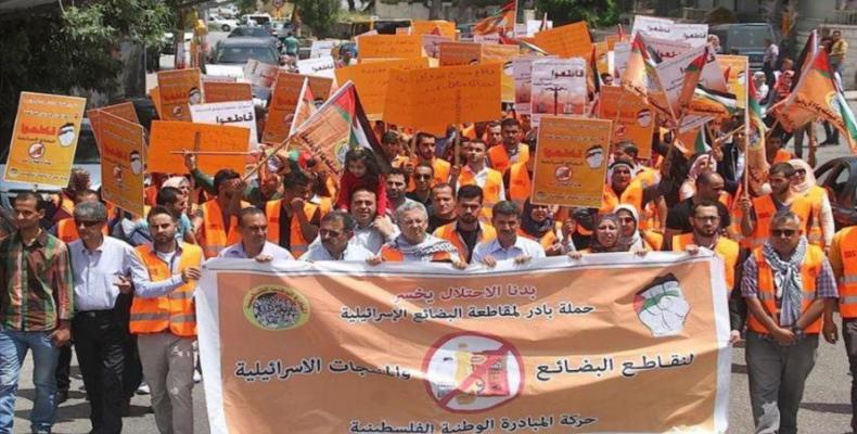 """Manifestantes palestinos sostienen banderas nacionales y pancartas en las que se lee en árabe: """"boicotear los productos israelíes, la campaña de iniciativa"""