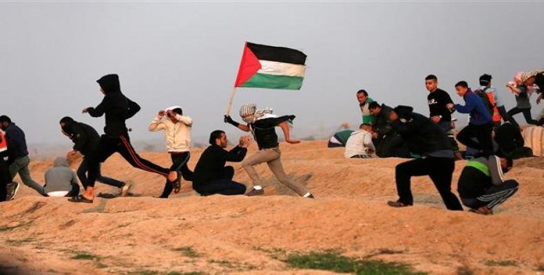 Palestinian protesters wave national flags as they participate in a demonstration on the beach near the maritime border with Israel, in the northern Gaza Strip.