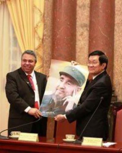 Ulises Guilarte (I) sostiene junto a Truong Tan Sang (D), una foto de Fidel Castro. Foto: EmbaCuba-Vietnam