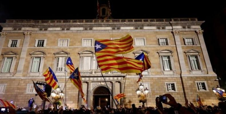 People celebrate and wave Catalan separatist flags in front of the Catalan regional government headquarters after the Catalan regional parliament declared indep
