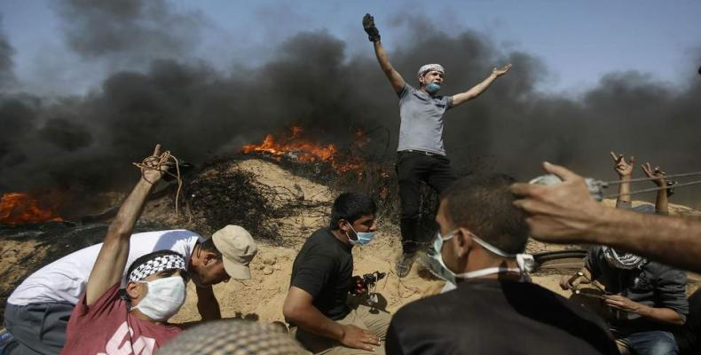 Palestinians take cover near the Gaza Strip's border with Israel during a protest in the Gaza.