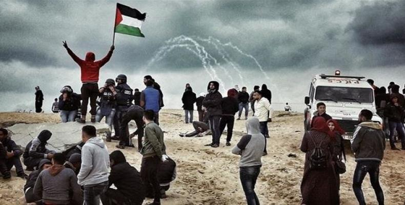A Palestinian protester waves a national flag as people participate in a demonstration on the beach near the maritime border with the Israeli-occupied territor