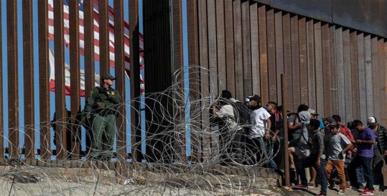 Central American migrants look through a border fence as a US Border Patrol agent stands guard near the El Chaparral border crossing in Tijuana, Mexico, on Nove