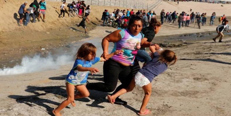 Maria Meza, a 39-year-old Honduran woman, runs with her two daughters as tear gas spreads.  Photo: Reuters