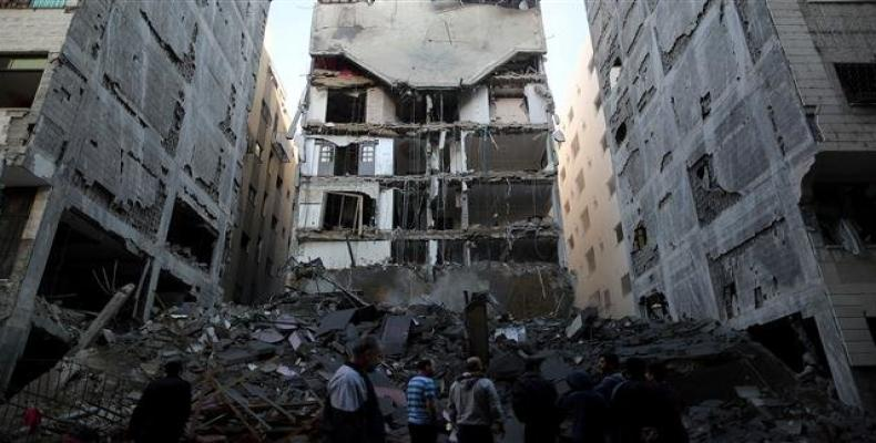 Palestinians gather near the remains of a building that was completely destroyed by an Israeli airstrike in Gaza City on November 13, 2018.  Photo: Reuters