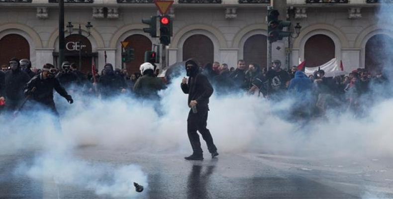 Greek university students are seen amid tear gas as they clash with riot police in Athens. (Photo: Reuters)