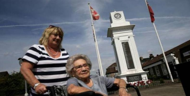 An elderly resident is wheeled past the World War 1 memorial near the civic square in the dock town of Tilbury in Essex, east of London.  Photo: AFP