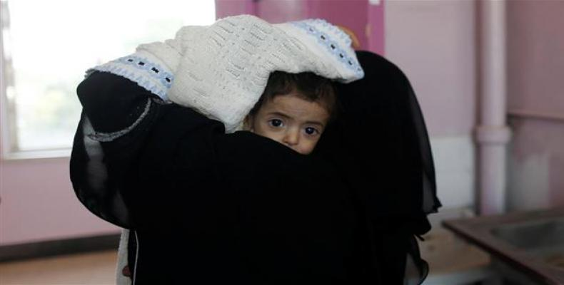 A woman carries a child at the malnutrition ward of al-Sabeen hospital in Sana'a, Yemen.  Photo: Reuters