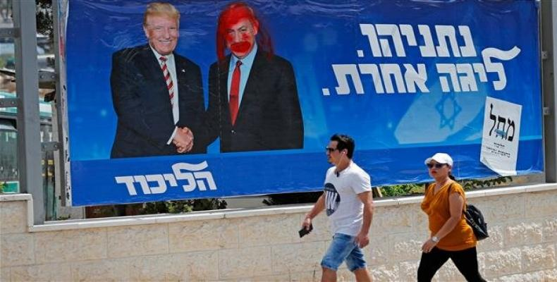 A defaced election billboard for the Likud party showing Donald Trump shaking hands with Netanyahu.  (Photo: AFP)