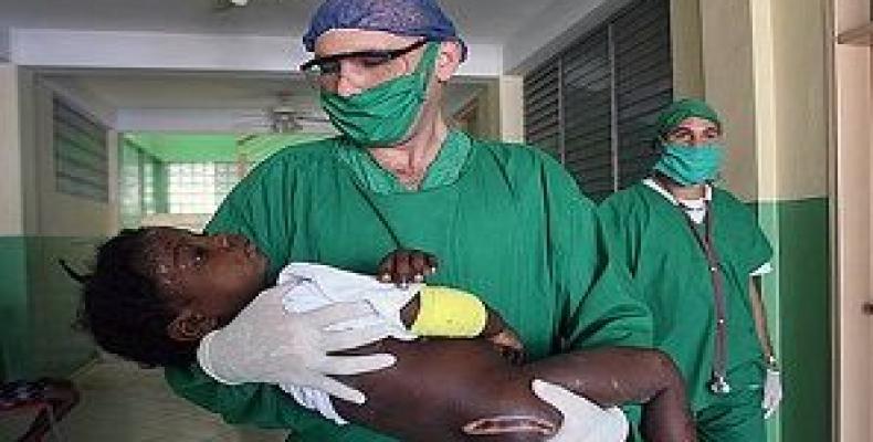 Kuba kuracisto prizorgas haitian knabinon. Foto: Cubadebate