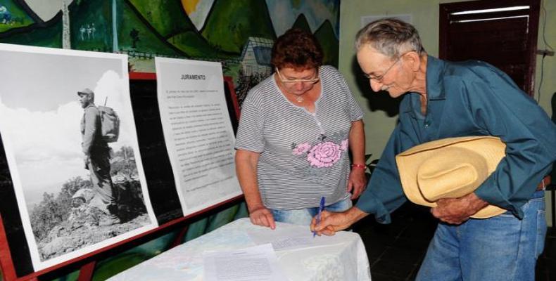 Campesino firma su compromiso con Fidel.  Foto: Diario Granma