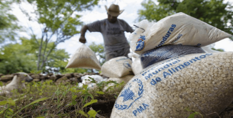 A farmer moves bags of provisions, donated by the United Nations World Food Program (WFP), during a distributing of food aid to families affected by the drought