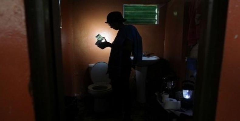 Ana Perez uses a solar lamp inside the bathroom of her home in Naguabo, Puerto Rico, on Jan. 27, 2018.  Photo: Rueters